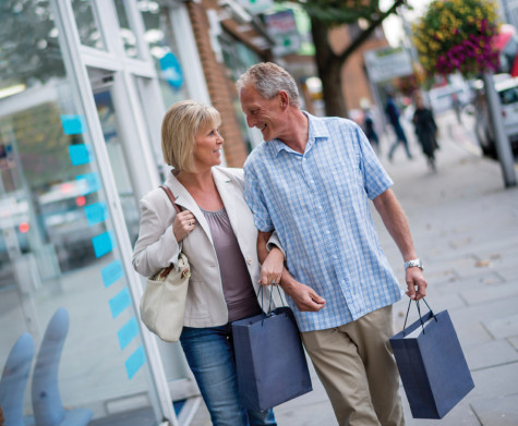 Shopping couple looking happy carrying bags