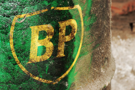 Celje, Slovenia - April 19, 2012: Old British Petroleum logo on a green barrel covered by oil. British Petroleum is third largest energy company in the world. BP was involved in many major environmental incidents including Deepwater Horizon oil spill which was the largest oil spill to date in petroleum industry. This shield style logo was used since 2002.